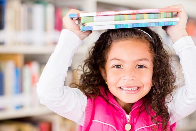 Happy girl at the library holding books